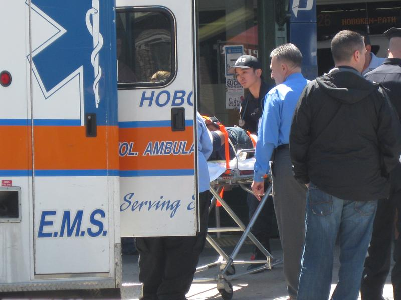 Emergency personell load a passenger from the PATH train crash into an ambulance.